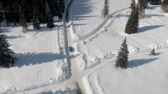 AERIAL: Auto driving towards beautiful winter ski resort on snowy plateau video