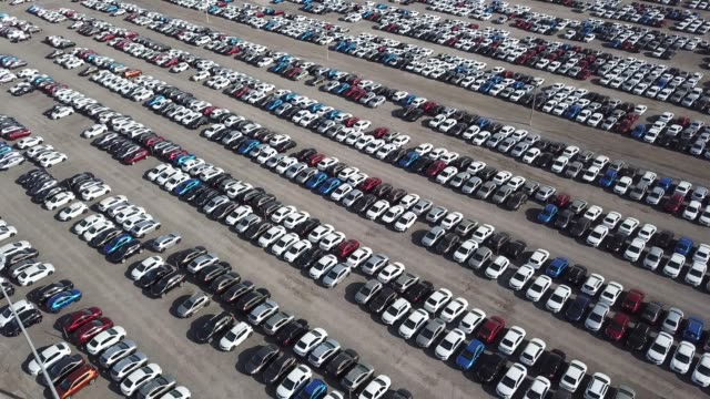 Auto Market or Car Parking Vehicles Ready for Further Distribution Aerial shoot of car parking. Flying over industrial zone with big parking lot of brand new cars. Many cars waiting for sale and transportation. Automobile industry. car salesperson stock videos & royalty-free footage