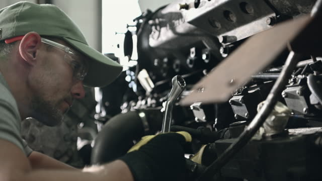 auto mechanic adjusting engine parts with wrenches. - затягивание стоковые видео и кадры b-roll