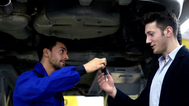 vídeos de stock e filmes b-roll de auto mecânico e cliente na loja de reparação auto - fundo oficina