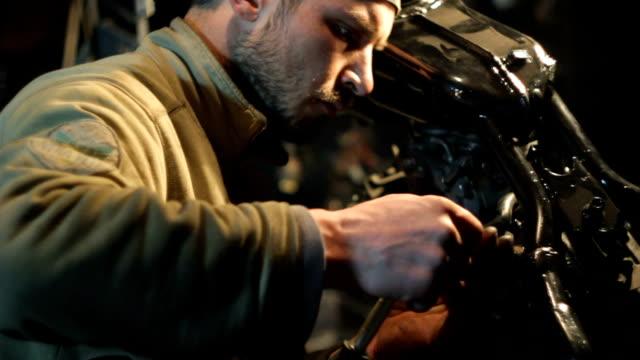 vídeos de stock e filmes b-roll de mecânico de carros junta personalizado motociclo em sua oficina - fundo oficina