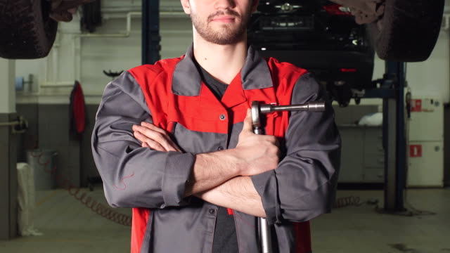 Auto mechanic crossed hands and looking at camera while standing under lifting car in repair garage video