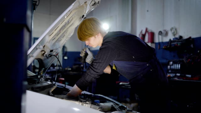 auto mechanic is checking internal faults in important car systems and robustness of connections, in automobile repair workshop - затягивание стоковые видео и кадры b-roll