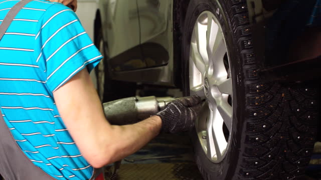 Auto Mechanic Is Twisting Bolts of a Wheels on an Automobile, Raised By Lifting Equipment video
