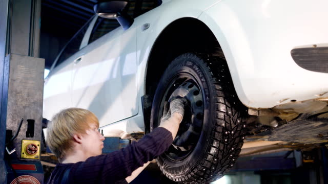 auto mechanic is twisting manually bolts of a wheels on an automobile, raised by lifting equipment in auto-service video