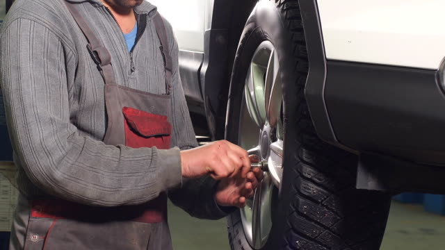 Auto Mechanic Is Twisting Manually Bolts of a Wheels on an Automobile, Raised By Lifting Equipment video