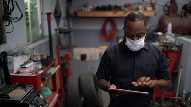 vídeos de stock e filmes b-roll de auto mechanic man walking using digital tablet at car repair shop - afro latino mask