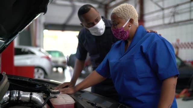 vídeos de stock e filmes b-roll de auto mechanic partners working at car repair - afro latino mask