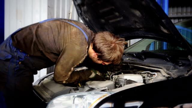 Auto mechanic repairing car starter system under hood.