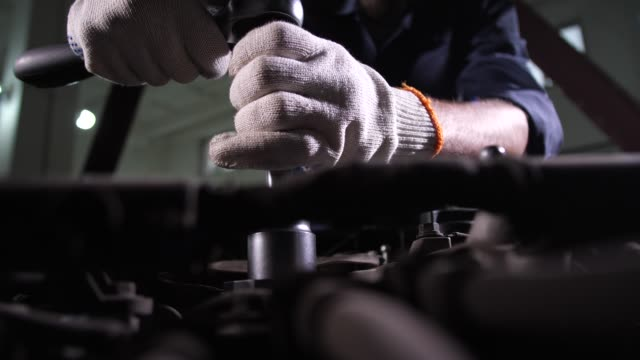 Auto mechanic replacing car oil filter during work Closeup of repairman's hands working on replacement of oil filter in car repair service. Auto repair specialist using wrench while going to change oil filter during vehicle maintenance in car workshop wrench stock videos & royalty-free footage