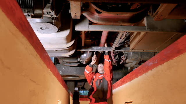 bilmekaniker skruva muttern under botten av lastbil - mekaniker bildbanksvideor och videomaterial från bakom kulisserna