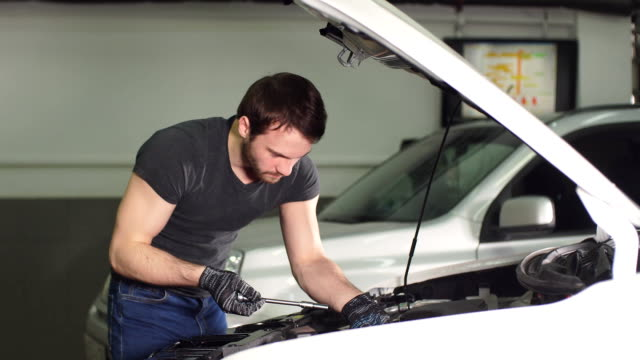 Auto mechanic testing electrical system on automobile video