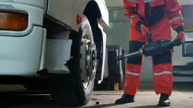 Auto mechanic unscrew the tire with pneumatic screwdriver video