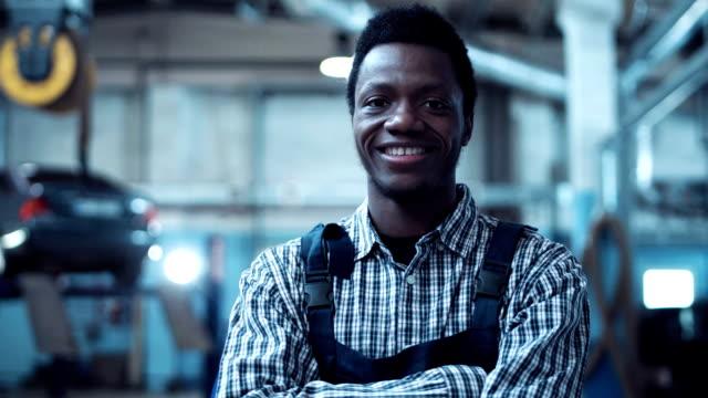 Auto mechanic wearing striped shirt smiles video