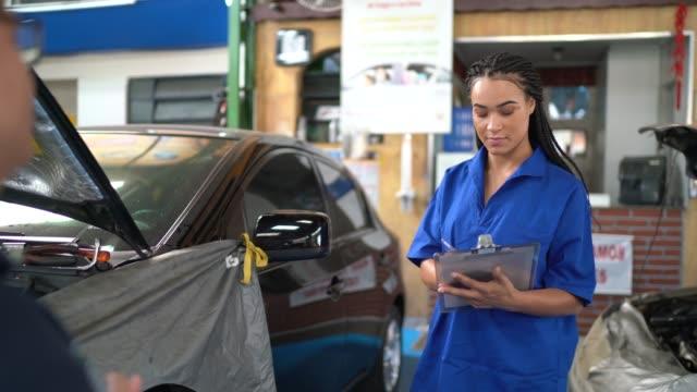 donna meccanico automatica che fa una lista di controllo dei clienti nell'officina di riparazione automatica - mechanic video stock e b–roll