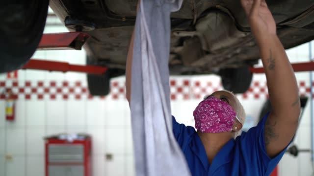 vídeos de stock e filmes b-roll de auto mechanic woman exhausted at auto repair shop - afro latino mask