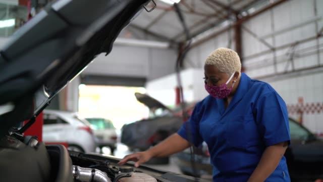 vídeos de stock e filmes b-roll de auto mechanic woman working at car repair - afro latino mask