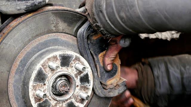 Auto mechanic working on brakes in car repair shop video