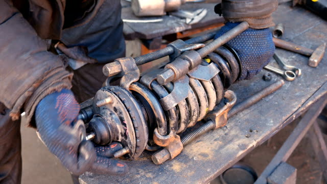 Auto mechanic working on shock absorber in garage video