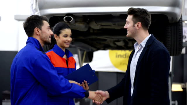 Auto mechanics and customer in auto repair shop video