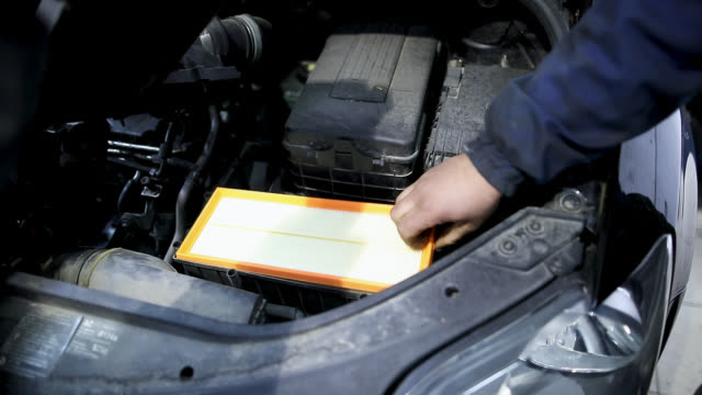 Auto mechanics changing air filter in garage Auto mechanics changing air filter in garage vehicle part stock videos & royalty-free footage