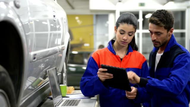 auto meccanico al lavoro con tecnologie digitali - mechanic video stock e b–roll