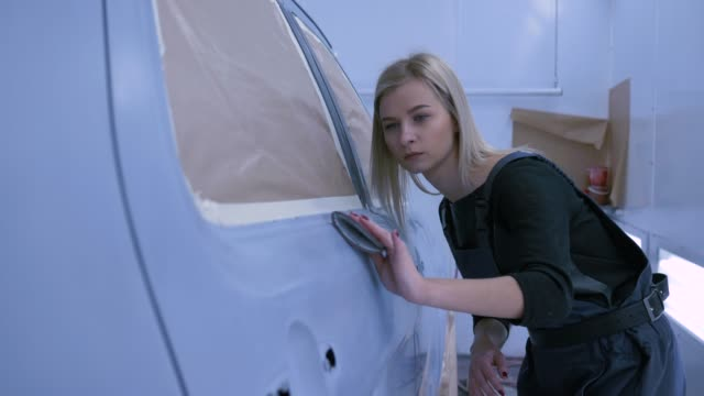 Auto painter sanding car paint by hand and smiles at paint chamber during repair work