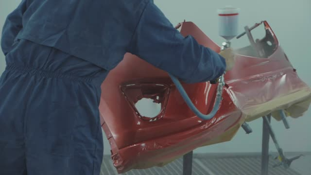 Auto painter spraying red paint on car front bumper in special booth video