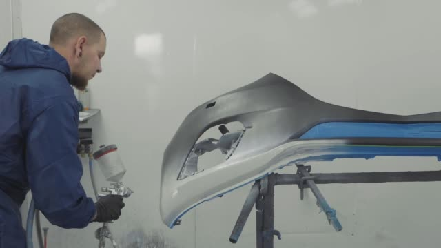Auto painter spraying white paint on car front bumper in special booth video