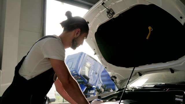 auto repairman in slow motion, men in backlight, mechanician repair video