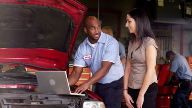 Auto repairman shows customer laptop computer video
