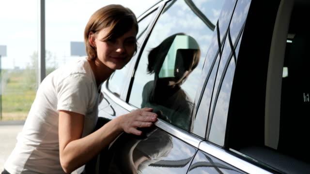 stockvideo's en b-roll-footage met auto verkoop centrum, jonge vrouwelijke klant staat volgende auto, gelukkig - bewondering