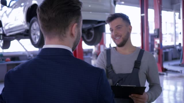 auto service, mechanic explaining expenses for car repair to his client writes in clipboard and shaking hands on background automobile on lift