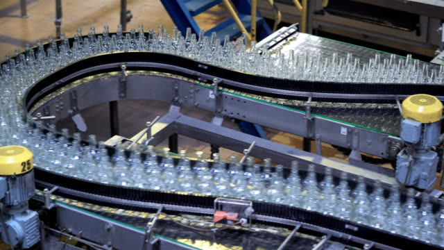 automated industrial chain of bottles drinks. industry automation and robots video