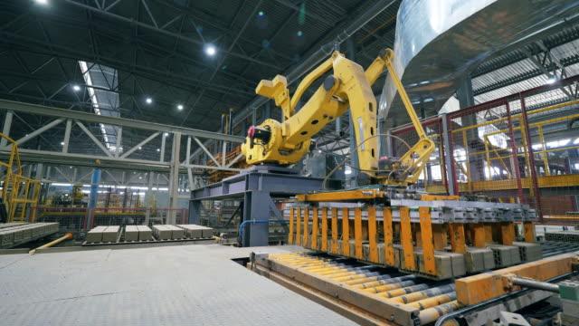 la macchina automatizzata sposta i mattoni su un trasportatore funzionante. - cemento video stock e b–roll