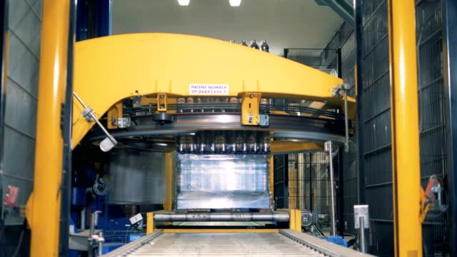 Automated machine wraps bottles, close up.