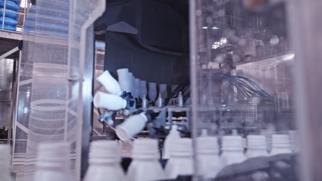 automated robotic arms moving the empty milk bottles at a diary factory - quality video stock e b–roll