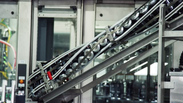 automatic canning machine transports aluminum cans with a conveyor belt in an indoor manufacturing facility - azionare video stock e b–roll