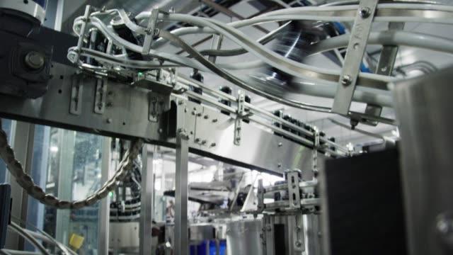 otomatik konserve makinesi, kapalı üretim tesisinde konveyör bant ile alüminyum kutular taşır - gıda ve i̇çecek sanayi stok videoları ve detay görüntü çekimi