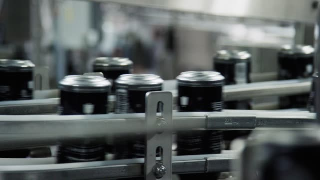 automatic canning machine transports aluminum cans with a conveyor belt in an indoor manufacturing facility - attrezzatura industriale video stock e b–roll