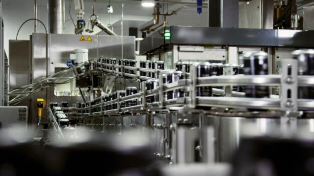 automatische canning-maschine transports aluminiumkannen mit einem fördergürtel in einer indoor-fertigung - aluminium stock-videos und b-roll-filmmaterial