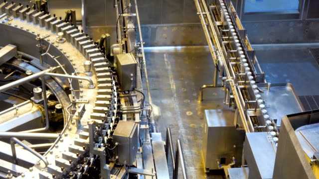 automatic canning machine transports aluminum cans with a conveyor belt in an manufacturing facility. - metal robot in logistic factory video stock e b–roll