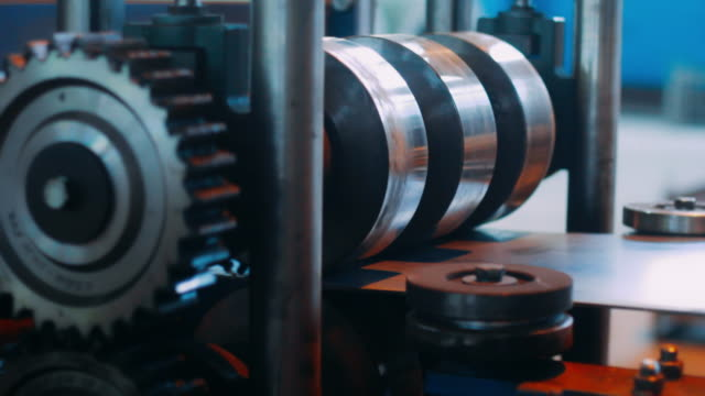 Automatic cold rolled technology for metal profiling Automatic cold rolled technology for metal profiling. Close up complex mechanism with rotating rollers and gears. Process of profile forming from steel sheet. Industrial production steel products steel mill stock videos & royalty-free footage
