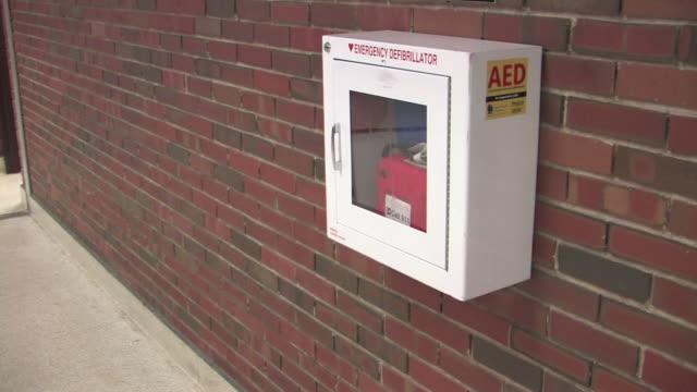 Automatic External Defibrillator (AED) HD Automatic External Defibrillator in case on wall with signage. defibrillator stock videos & royalty-free footage