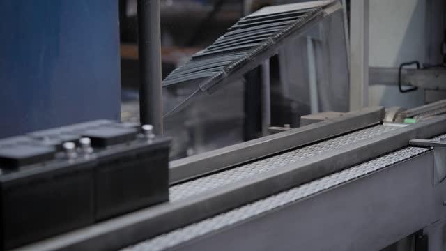 stockvideo's en b-roll-footage met automatische lijn voor de assemblage van autobatterijen. de zwarte batterijen bewegen en verzamelen zich op de transportband - lood