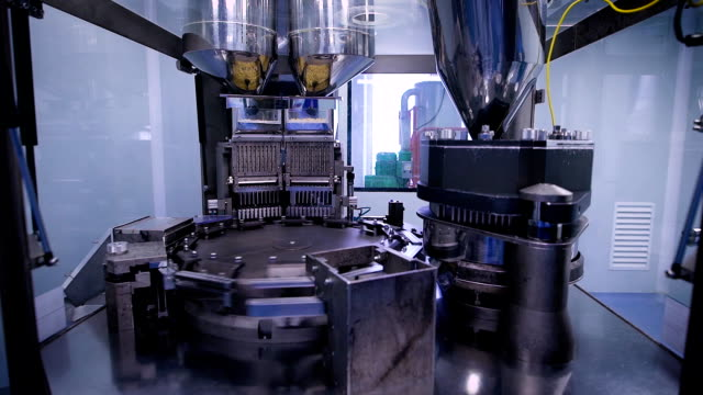 Automatic production line at a pharmaceutical company. The machine fills the capsule with contents video