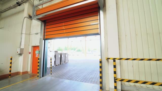 vídeos y material grabado en eventos de stock de puertas del rodillo automático del color naranja son bajando hacia abajo en el almacén de planta de carpintería. - puerta entrada