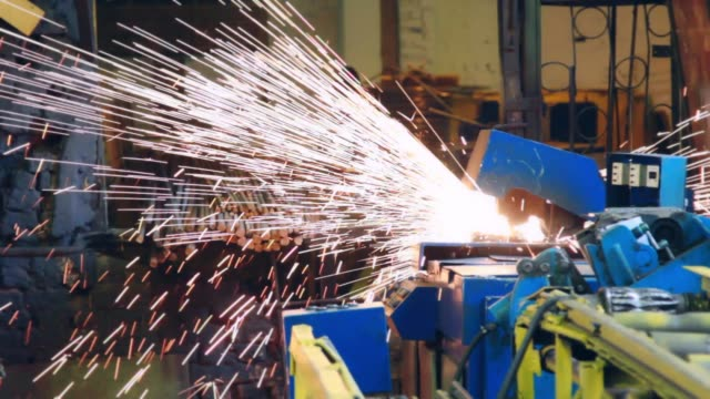 Automatic welding machine working at factory. Bright metal sparks throwing Automatic welding machine working at factory. Bright metal sparks throwing during metalworking. Heavy industry equipment for steel construction manufacturing grind stock videos & royalty-free footage
