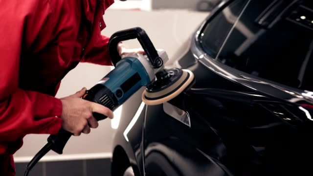 automechanic polishing a black new car. cleaning the new vehicle. - lucidare video stock e b–roll