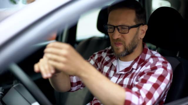 vídeos de stock, filmes e b-roll de motorista de automóvel a sentir dor no pulso, inflamação das articulações, osteoartrite, saúde - punho